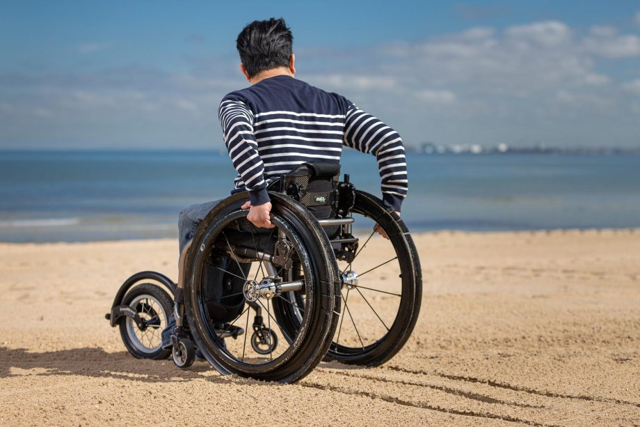 A man in a wheelchair using along the sand towards the beach, with sunny blue skies behind him.